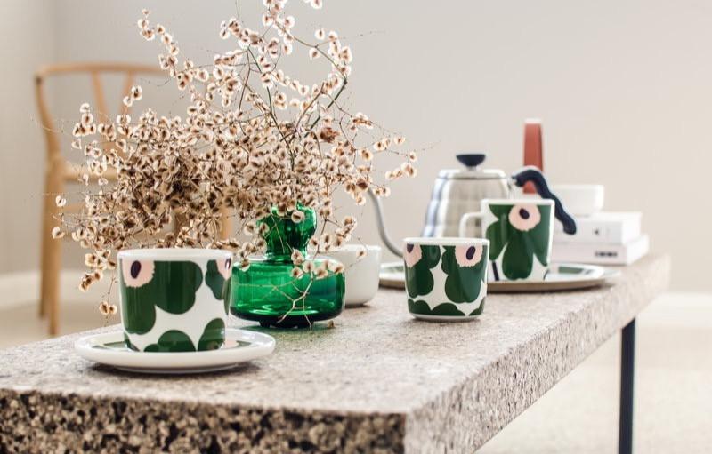 Marimekkos Unikko-Muster (Poppy) in frischem Weiss, saftigem Grün und Pfirsichtönen erinnert an einen blühenden Sommergarten, der von einer pfirsischfarbenen Nachmittagssonne beleuchtet wird.