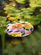 Das wunderschöne Rosarium-Motiv ist in fröhlichen Blau-, Gelb- und Rosatönen und wurde von Aino-Maija Metsola entworfen. Das Motiv illustriert einen Rosengarten, in dem die volle Blüte bald vorbei sein wird. Die Blütenblätter fallen bereits im Herbstwind. Das Muster zeigt verschiedene Rosensorten, aber Rugosa-Rosen überwiegen. Rugosas befinden sich auch vor dem Haus des Designers.
