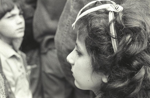 Kislány a Kossuth téren, hajában nemzeti színű szalag.