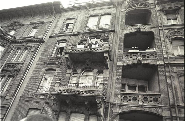 A Margit-híd budai hídfőjénél lévő Lipthay utcai erkélyekről, ablakokból nézik a felvonulókat.