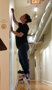 """Lindsey removing vinyl from the title wall of the """"Tributaries: Jill Baker Gower 
