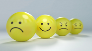 4 yellow balls with 3 looking worried and stressed and one smiling.