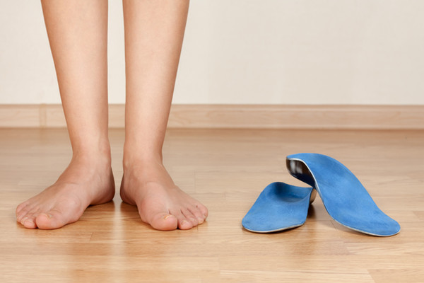 woman barefooted standing next to a pair of orthotic inserts