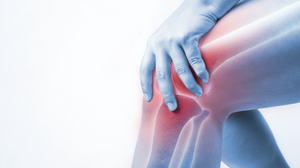 Person holding knee showing xray image of knee red with pain