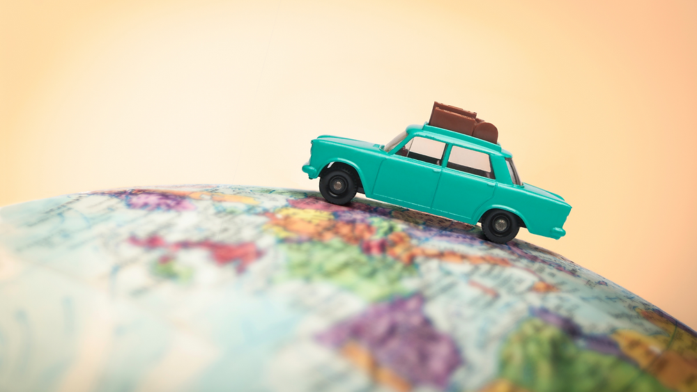 toy car on world globe indicating travel by car
