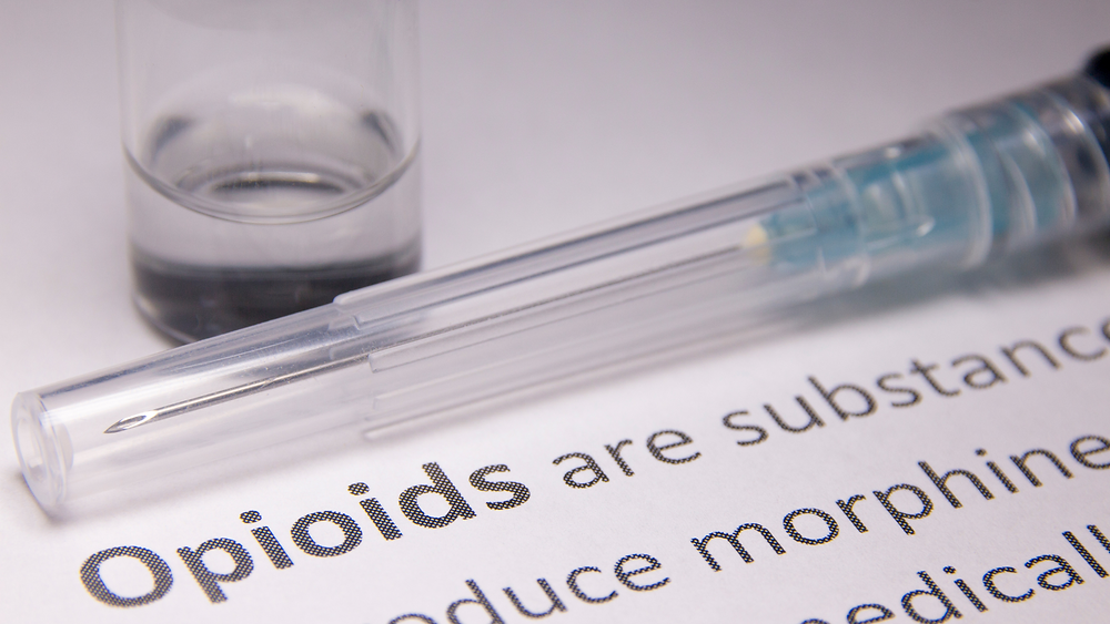 a needle sitting on paper with the text opioids