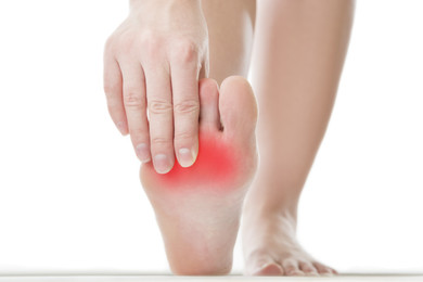 woman touching bottom of foot. Foot shows red with pain.