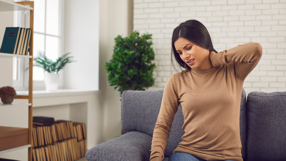 woman seated on couch holding neck in pain