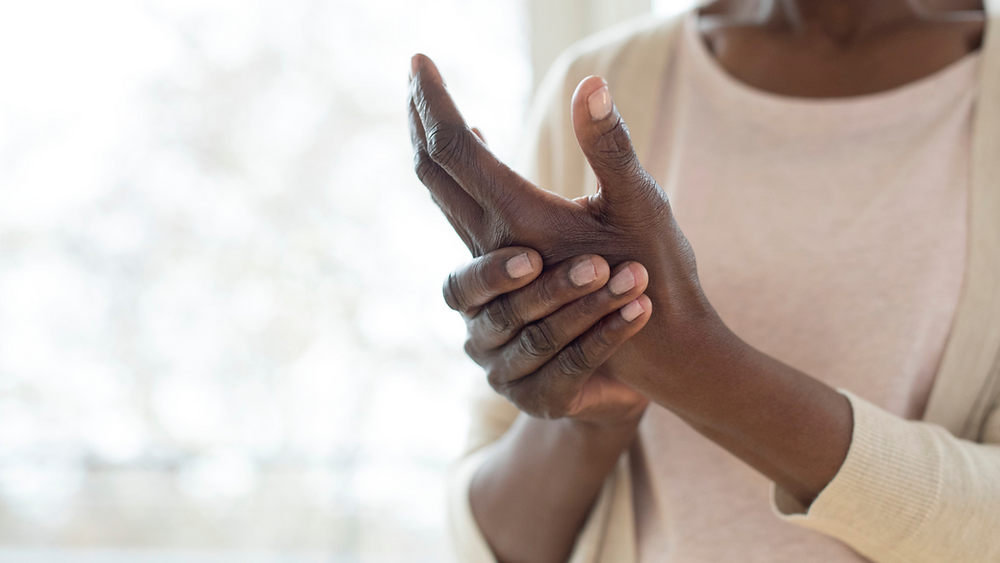 woman holding her hand showing joint pain, arthritis