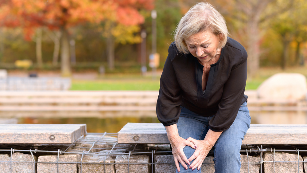 older woman sitting, holding knee showing pain from osteoarthritis