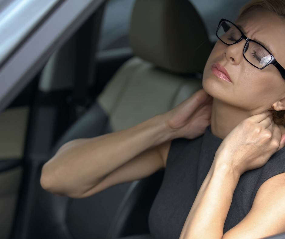 woman in car holding neck - whiplash