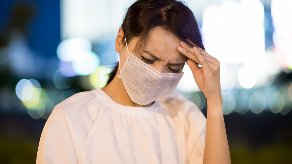 women in face mask holding forehead for headache