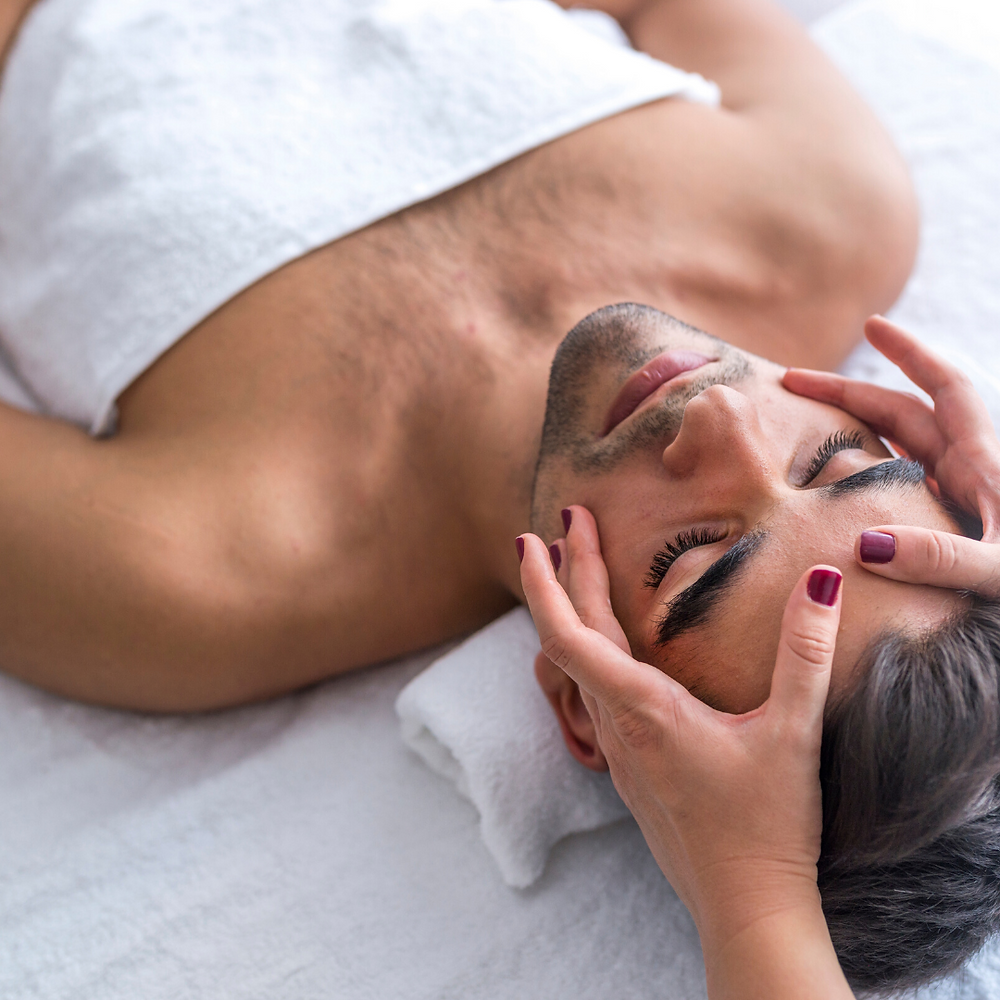 man on massage table getting face massaged for stress relief