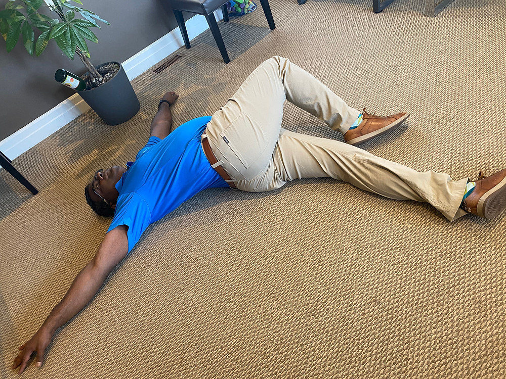 Dr. Andre demonstrating lying knee-roll-over lower back stretch