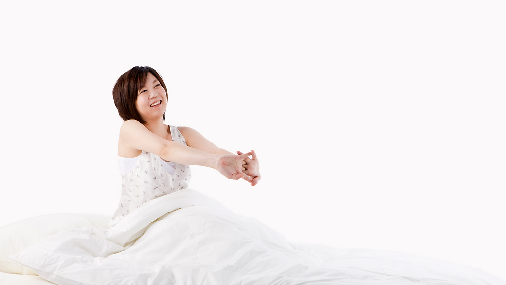 Asian woman waking in bed looking rested after sleep