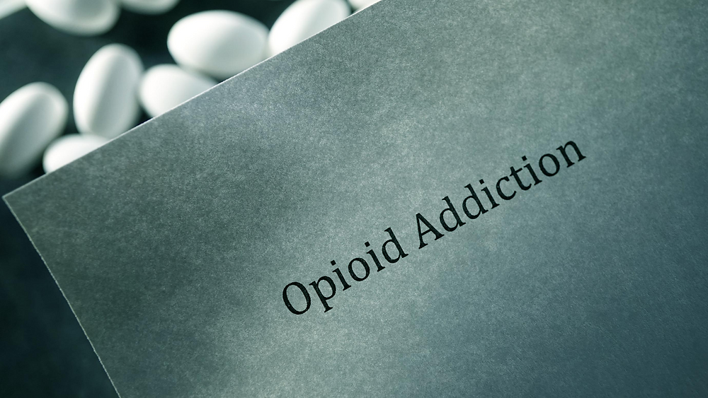 typed page that says Opioid Addiction with pills behind it