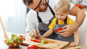 father and small son slicing tomato on cutting board.