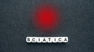 dice spelling out sciatica with red dot above