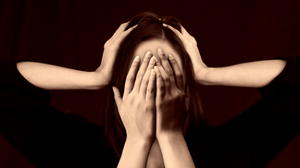 woman with hands over eyes and another set of hands holding her head on either side - headache