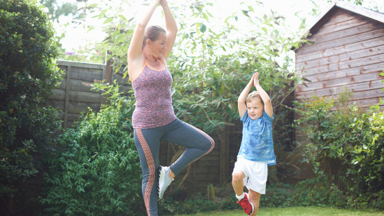 Mother and small child exercising in the home yard.