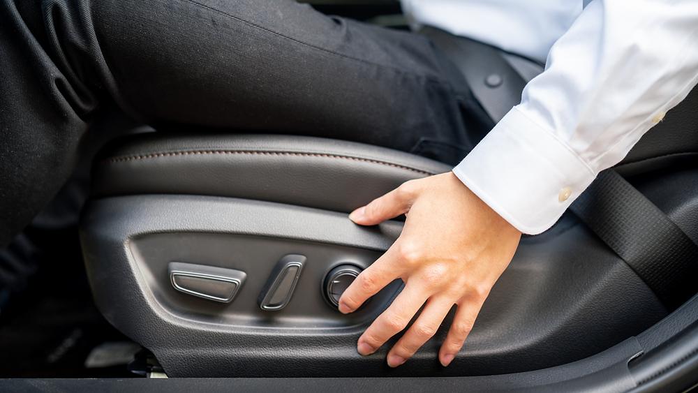 Man adjusting drives car seat to show proper seat ergonomics