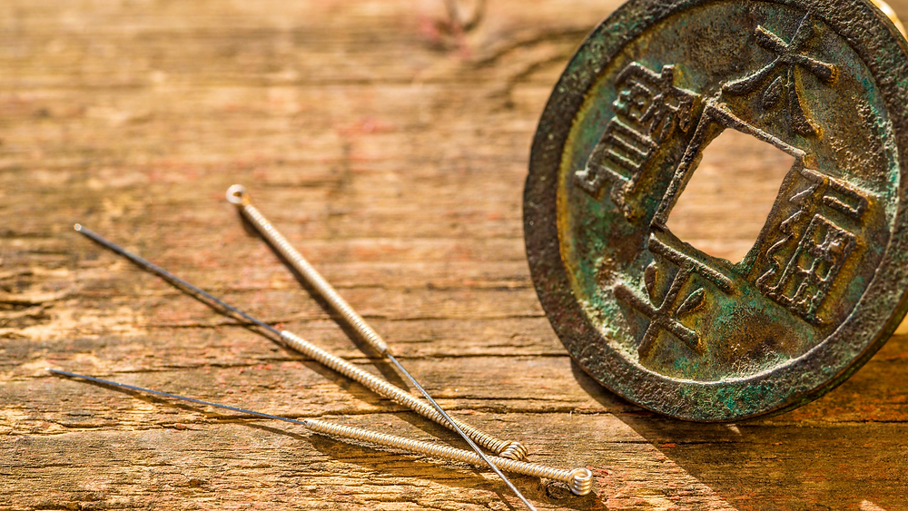 acupuncture needles and ancient coin
