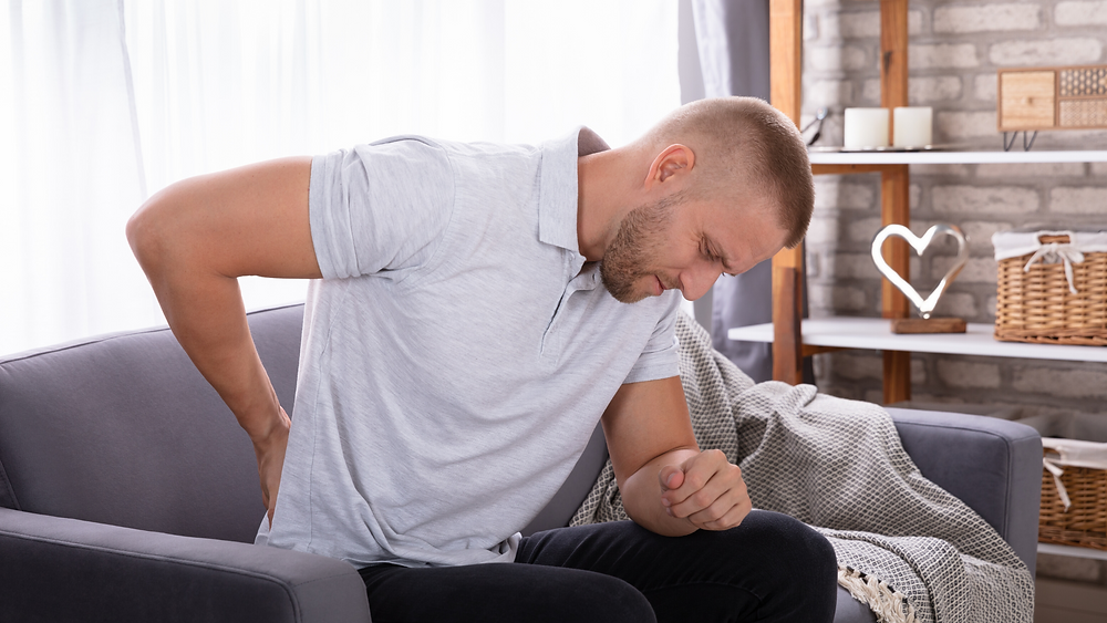 man on couch with hand on low back with sciatic pain from sciatic nerve
