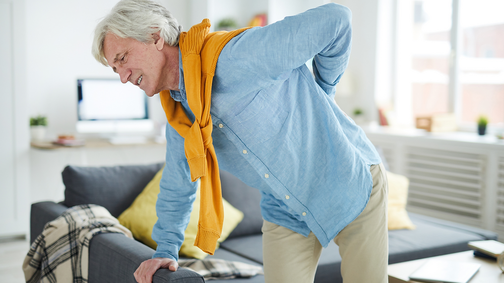 man leaning over couch with hand on back in pain
