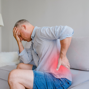 man sitting with hand on lower back showing red light indicating back pain