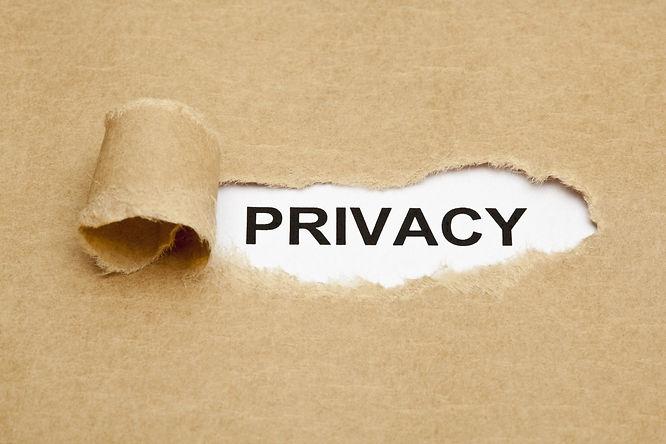 The word Privacy appearing behind torn brown paper..jpg