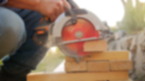 construction-worker-cutting-wood-with-ci