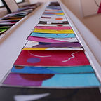 Small paper artworks sitting on top of one another on a windowsill, a rainbow of colours