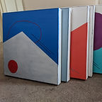 Collection of canvases, stacked standing upright. Blue, Grey, Orange and Teal colours