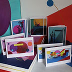 A collection of cards and original artworks on display, very colourful and warm