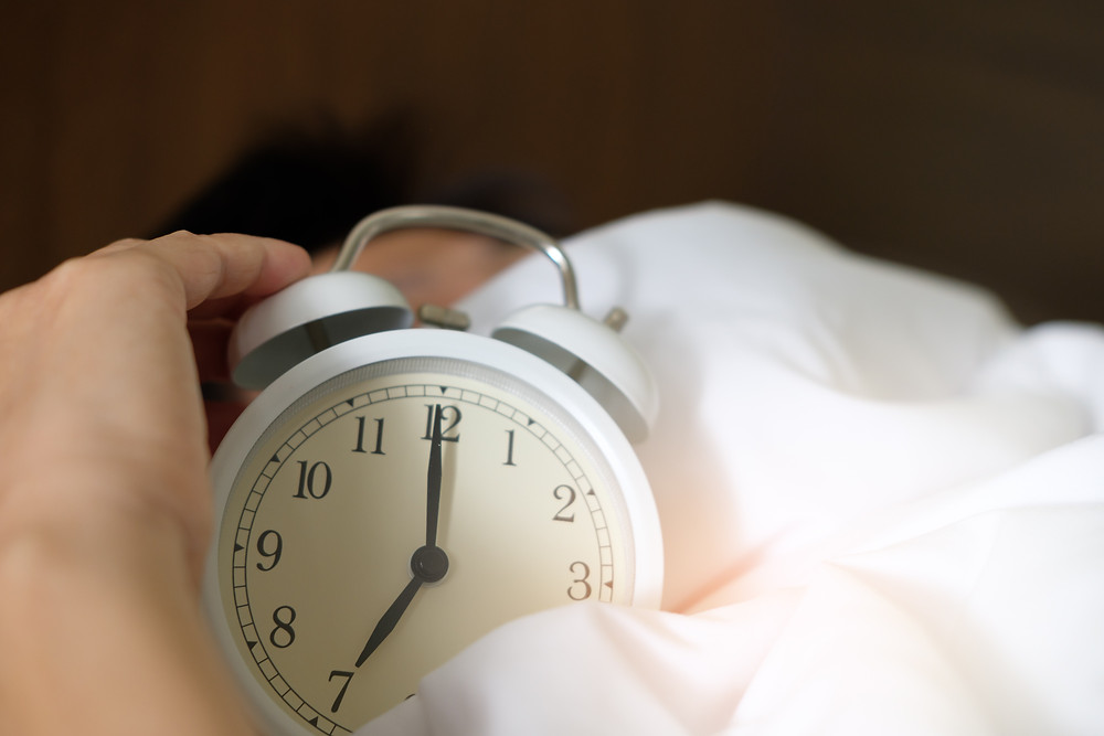 man reaching for an alarm clock in bed