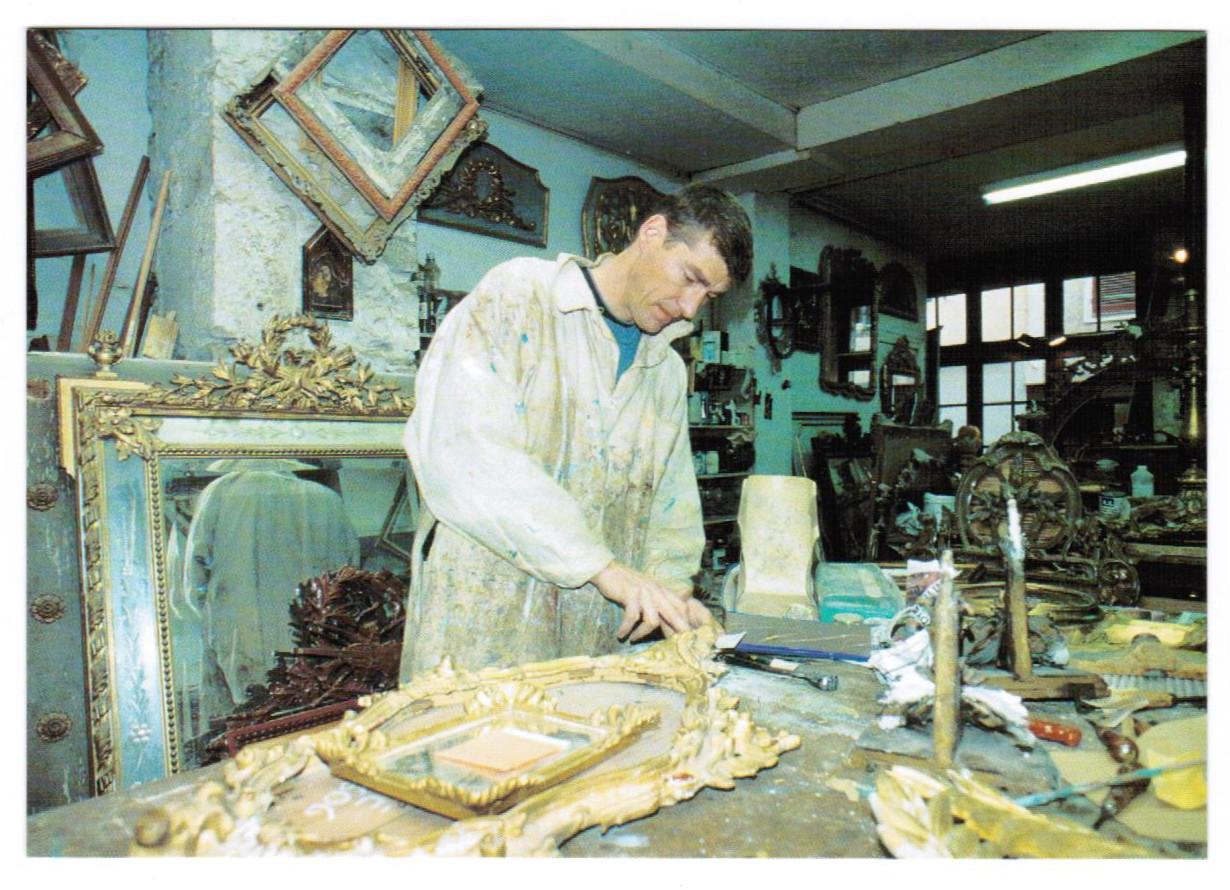Carte postale avec une photographie de David Jousselin, doreur sur bois à Bayonne (Pyrénées-Atlantiques) en train de restaurer un miroir ancien, août 2000. Archivage atelier Or Cadre, Laetitia Nicolas, Lodève.