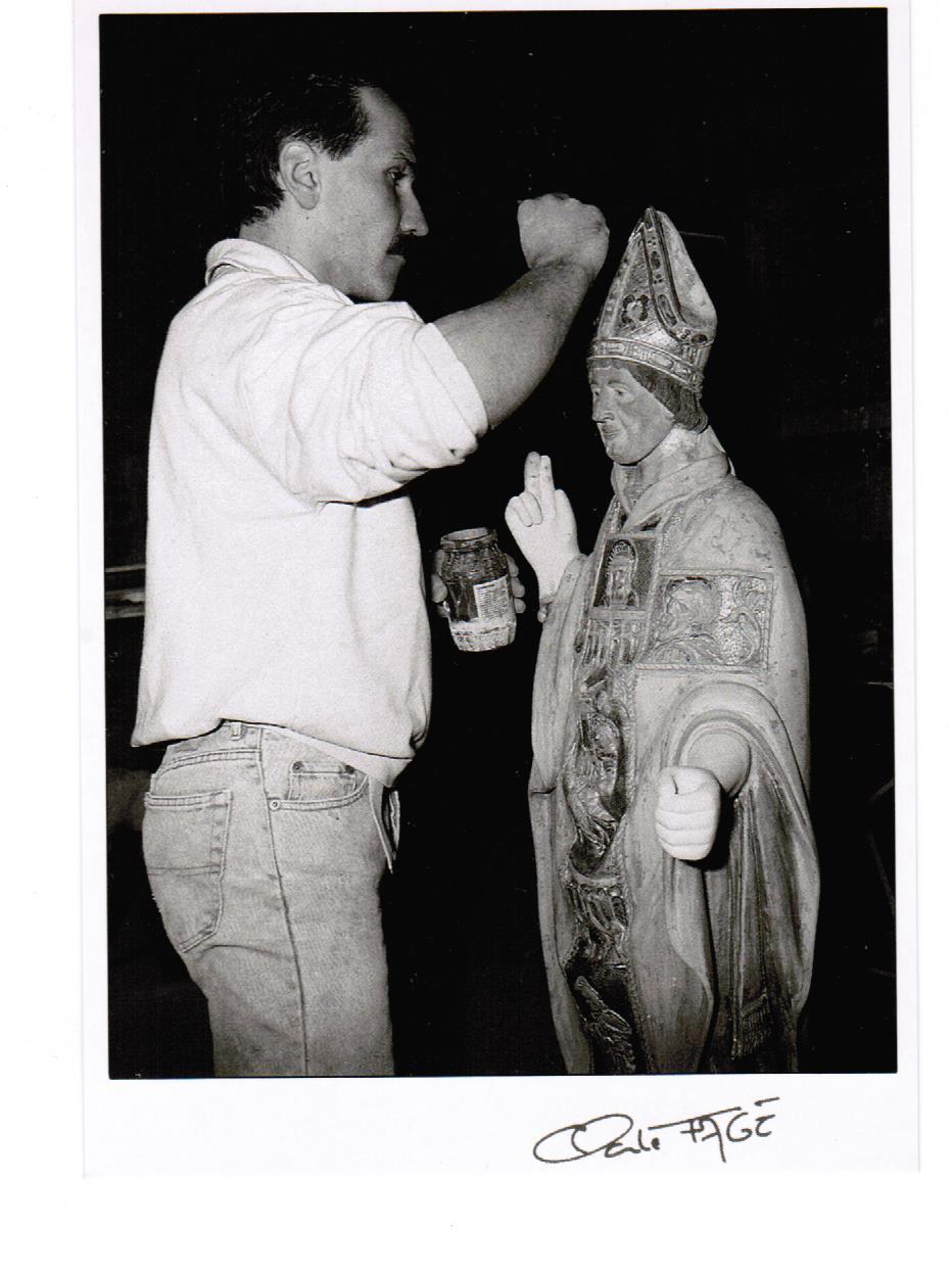 Déroulement d'un travail de restauration en dorure d'une statue de Saint Clair par Bertrand Lotteau, qui après différents stages (8 ans de formation) chez des Maîtres Doreurs-Laqueurs, s'est installé en 1989 à Vaux en Pré en Saône-et-Loire.  Troisième phase: les restaurations en bois finement poncées sont recouveertes de 3 couches d'assiette à dorer (terre naturelle rouge, brune ou noire, mélangée à de la colle de peau de lapin et d'eau). Photographie de Claude Fagé, 1992. Archivage atelier Or Cadre, Laetitia Nicolas, Lodève.