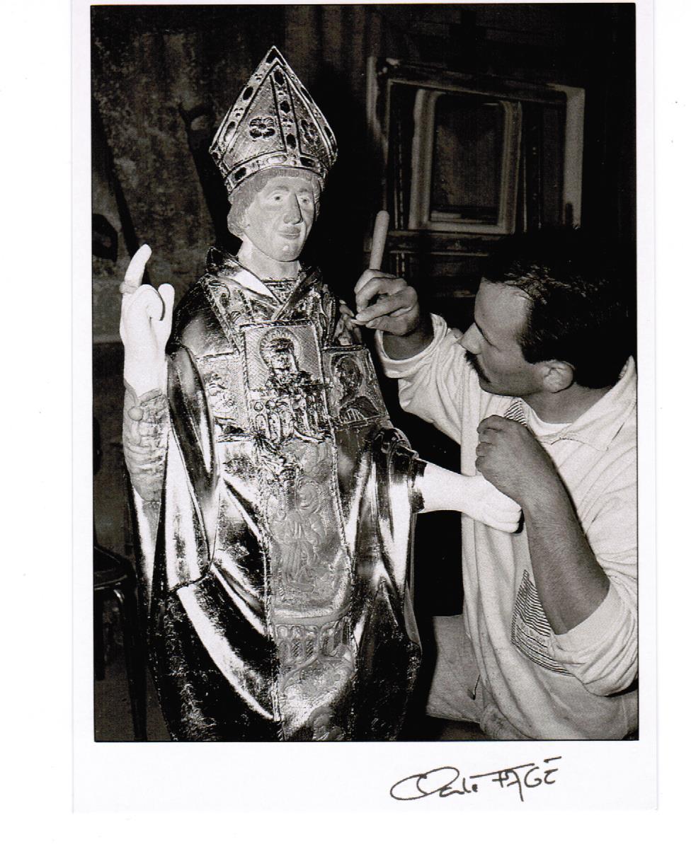 Déroulement d'un travail de restauration en dorure d'une statue de Saint Clair par Bertrand Lotteau, qui après différents stages (8 ans de formation) chez des Maîtres Doreurs-Laqueurs, s'est installé en 1989 à Vaux en Pré en Saône-et-Loire. La cinquième phase: les feuilles d'or une fois lissées sont brunies; c'est-à-dire qu'elles sont polies à la pierre d'agate. L'or obtient alors tout son éclat. Photographie de Claude Fagé, 1992. Archivage atelier Or Cadre, Laetitia Nicolas, Lodève.