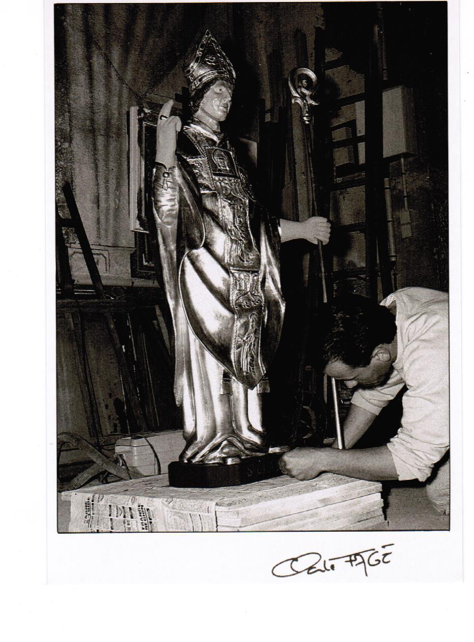 Déroulement d'un travail de restauration en dorure d'une statue de Saint Clair par Bertrand Lotteau, qui après différents stages (8 ans de formation) chez des Maîtres Doreurs-Laqueurs, s'est installé en 1989 à Vaux en Pré en Saône-et-Loire. La sixième et dernière phase, la dorure est encollée pour assurer la protection de l'or dans le temps. Photographie de Claude Fagé, 1992. Archivage atelier Or Cadre, Laetitia Nicolas, Lodève.