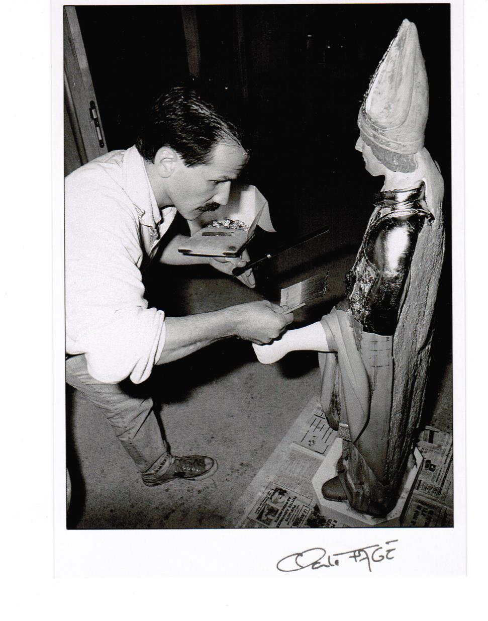 Déroulement d'un travail de restauration en dorure d'une statue de Saint Clair par Bertrand Lotteau, qui après différents stages (8 ans de formation) chez des Maîtres Doreurs-Laqueurs, s'est installé en 1989 à Vaux en Pré en Saône-et-Loire.  La quatrième phase est la pose des feuilles d'or. Photographie de Claude Fagé, 1992. Archivage atelier Or Cadre, Laetitia Nicolas, Lodève.