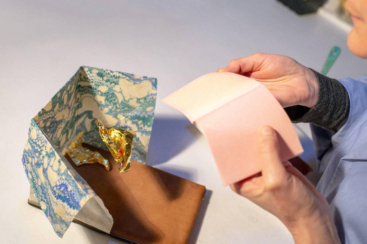 Souffler sur la feuille d'or pour la faire tomber du carnet dans le coussin (Laetitia Nicolas, Or Cadre, Lodève)