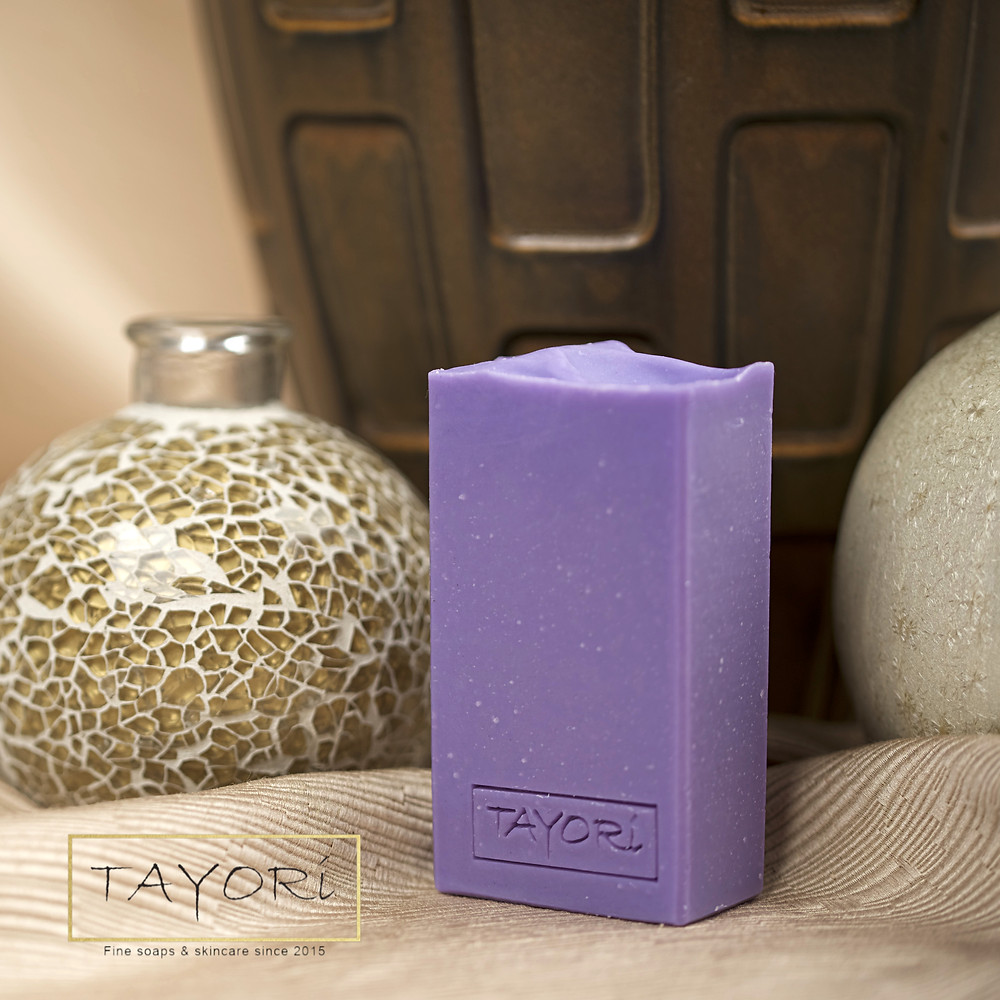 Purple bar of soap in front of three different vases