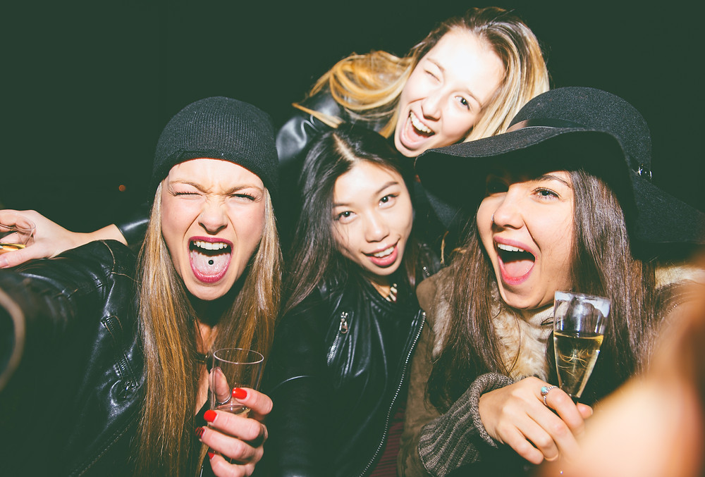 four girls taking crazy selfies who are also drinking