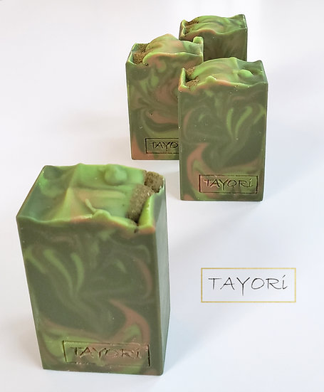 A dark green, light green & beige bar of soap made with beer with ground hops sprinkled on top for decoration