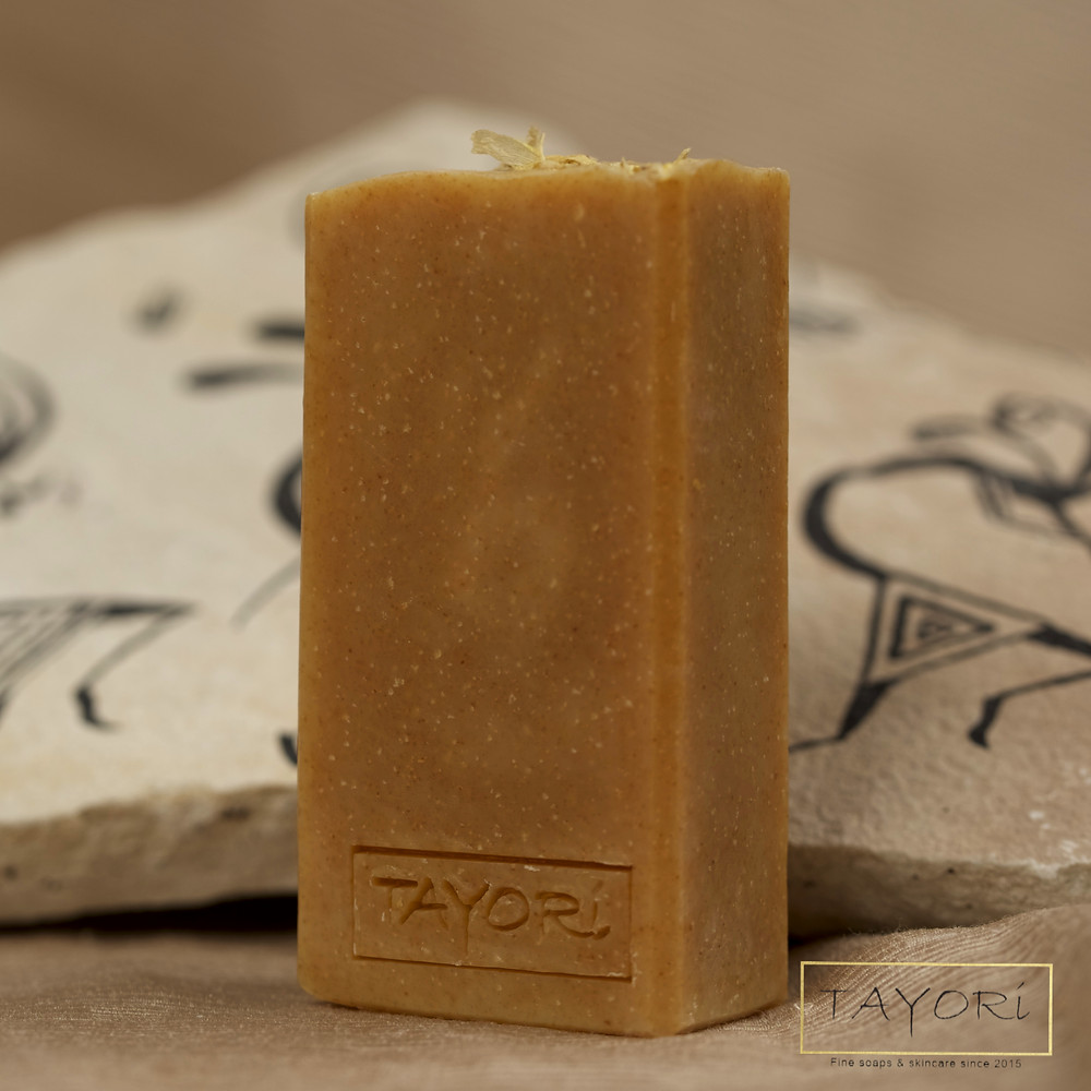 Orange bar soap with a stone with drawings of Kokopelli