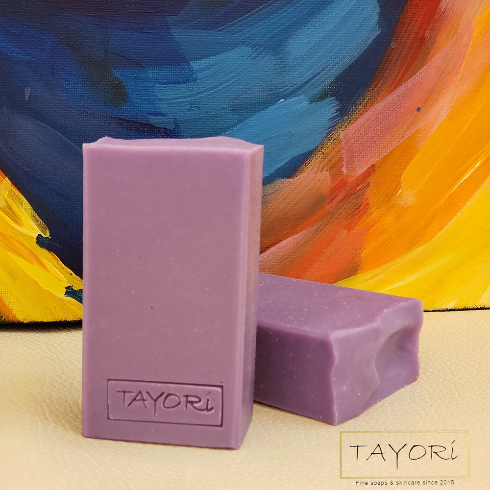 Two purple bars of soap in front of a corner of a painting with vibrant colors