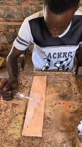Local artist painting the adhesive onto a piece of wood