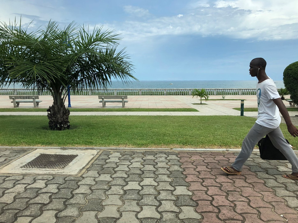 Guy walking fast along the ocean front walkway