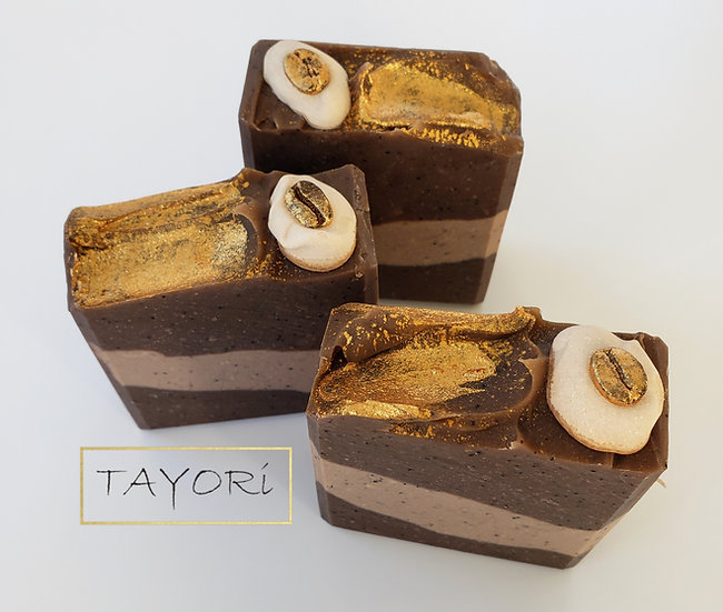 A brown and beige layered soap with gold brushed on top and a real coffee bean nestled in a dollop of cream (soap)