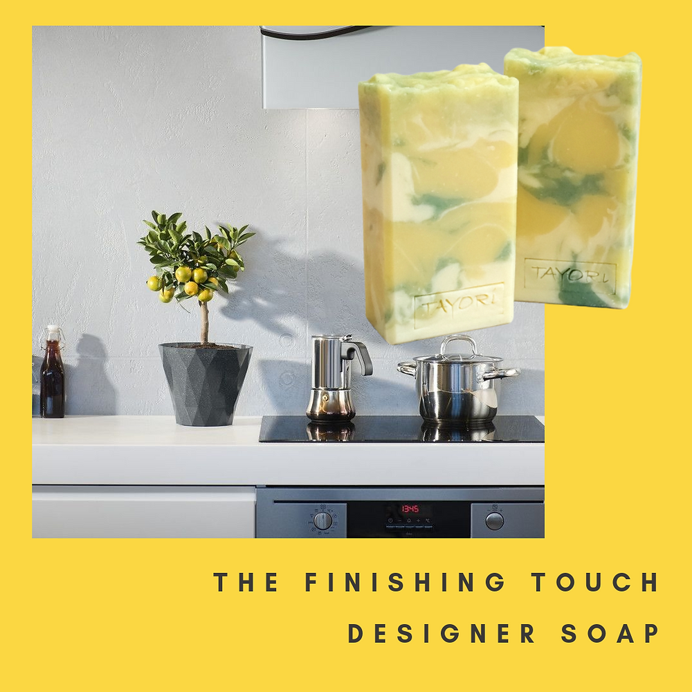 A modern monochromatic kitchen with a miniature lemon tree full of lemons and two bars of matching yellow soap
